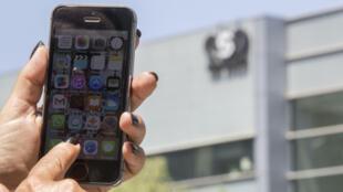 Una persona sujeta un teléfono frente a la sede de NSO Group en Herzliya, Israel. Fotografía de archivo.