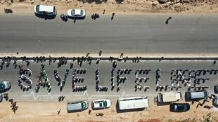 A human chain is formed in a vigil calling for maintaining a UN resolution authorising the passage of humanitarian aid into Syria's rebel-held northwestern province of Idlib through the Bab al-Hawa border crossing with Turkey, near Bab al-Hawa along the motorway linking it to Idlib on July 2, 2021.
