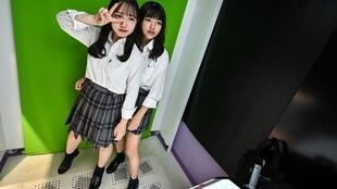 """Teenagers in Tokyo pose at a Japanese photo booth known as a """"purikura"""""""