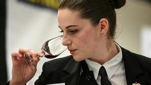 Chloe Laroche, 21, winner of the 27th contest for the best student sommelier, smells a glass of red wine during the contest in May 2019, in Tain l'Hermitage, southeastern France