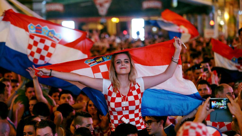 Una aficionada croata celebra en una plaza pública de Zagreb, la capital de ese país, junto a cientos de hinchas el triunfo de su selección ante la de Argentina por 3-0 y la clasificación a la siguiente ronda.