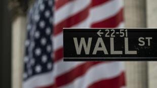 Un cartel de Wall Street frente a la fachada de la Bolsa de Nueva York, cubierta por una bandera de EEUU el 30 de abril de 2020