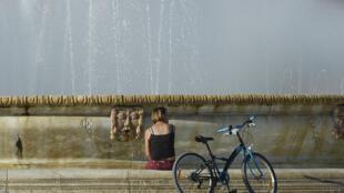 Una mujer se refresca en una fuente el 22 de junio de 2020 en la ciudad española de Sevilla