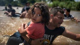 Luis Acosta lleva a Ángel Jesús de 5 años, ambos de Honduras, mientras una caravana de migrantes de América Central que se dirige a los Estados Unidos cruzó el río Suchiate a México desde Guatemala en Ciudad Hidalgo, México, el 29 de octubre de 2018.