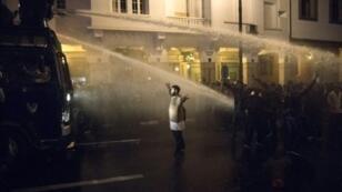 محتج مغربي رافعا يديه في مواجهة خراطيم مياه الشرطة أثناء تفريق الشرطة في الرباط في 24 آذار/مارس 2019 مظاهرة لأساتذة وقتيين يطالبون بعقود عمل دائمة