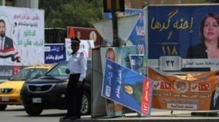 شرطي أمام لافتة انتخابية في بغداد 4 أيار/مايو 2018
