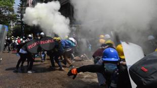 Des manifestants ripostent après des tirs de gaz lacrymogènes de la police, lors d'une manifestation à Rangoun, en Birmanie, le 7 mars 2021.