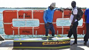 Deux hommes à proximité d'un cercueil à bord d'un bateau sur le lac Victoria, samedi 22 septembre 2018, en Tanzanie.