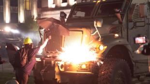 Un manifestante lanza fuegos artificiales a un vehículo blindado en Kenosha, Wisconsin, el 26 de agosto de 2020, en la tercera noche de disturbios para denunciar que la policía disparó contra el estadounidense Jacob Blake.
