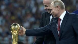 صورة وزعتها وكالة سبوتنيك للرئيس الروسي فلاديمير بوتين (يمين) يلامس كأس العالم وبجانبه رئيس الفيفا جياني إينفانتينو في 15 تموز/يوليو 2018