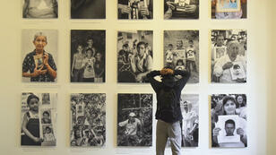 Un jóven colombiano se toma la cabeza ante la exposición de Jesús Abad en Bogotá, 05 de 11 de 2018
