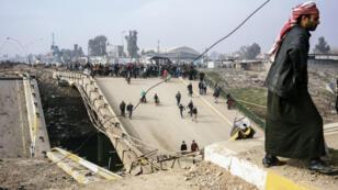 Des Irakiens traversent un pont détruit par les combattants de l'EI à Mossoul, le 21 janvier 2017.