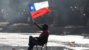 Un manifestante sostiene una bandera de Chile durante una protesta contra el modelo económico del Gobierno en Santiago, Chile, el 24 de octubre de 2019.