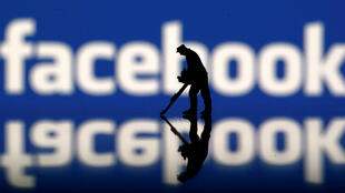 A figurine is seen in front of the Facebook logo in this illustration taken March 20, 2018.