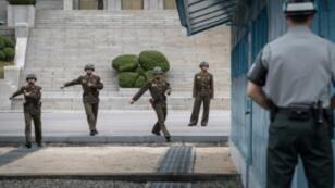 جندي كوري جنوبي (يمين) يقف أمام جنود كوريين شماليين يسيرون باتجاه خط ترسيم الحدود