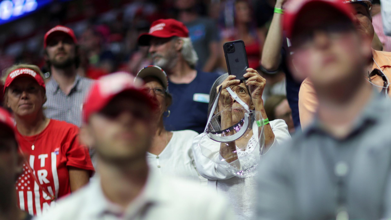 Un asistente mayor sostiene su máscara protectora colgando de su mano mientras los partidarios del presidente de los Estados Unidos, Donald Trump, escuchan su discurso durante una hora y media en la primera campaña de reelección del presidente en varios meses en medio de la enfermedad por coronavirus brote, en el Centro BOK en Tulsa, Oklahoma, EE. UU., 20 de junio de 2020.
