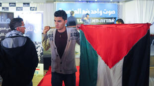 Un partisan de la Liste unifiée avec un drapeau palestinien au QG de campagne à Nazareth.