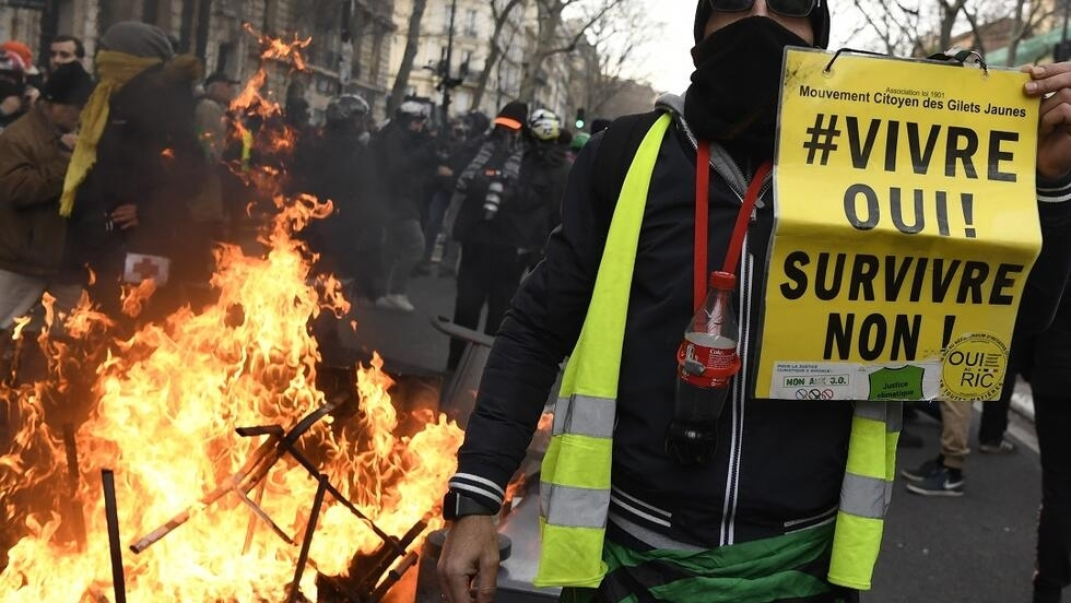 "A man holds a banner reading ""Yes to living ! No to surviving !"" as protesters demonstrate in Paris on January 11, 2020, as part of a nationwide multi-sector strike against the French government's pensions overhaul.  (Photo by Bertrand GUAY / AFP)"