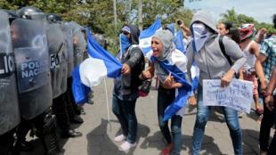 Un manifestante grita consignas a la policía antidisturbios durante una protesta contra el gobierno de Nicaragua  el presidente Daniel Ortega en Managua.
