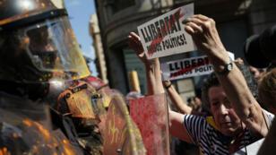 """Une femme demande la """"libération des prisonniers politiques"""" pendant des manifestations devant un centre de la police catalane à Barcelone, le 29 septembre 2018."""