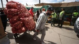 La policía realiza una campaña preventiva en un mercado al aire libre para ayudar a frenar la propagación del nuevo coronavirus, en Bogotá, Colombia, el jueves 23 de julio de 2020.