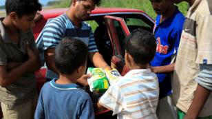 Un niño recibe un paquete de maíz en trueque por pescado en Rio Chico, Venezuela, Junio 14 de 2018.