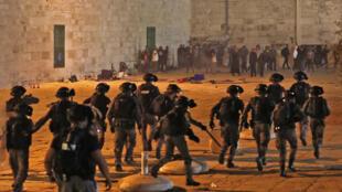 Las fuerzas de seguridad israelíes avanzan en medio de enfrentamientos con manifestantes palestinos en el complejo de la mezquita de Al-Aqsa, en Jerusalén, el 7 de mayo de 2021.