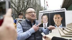 Louis Huang of Vancouver Freedom and Democracy for China holding photos of Canadians Michael Spavor and Michael Kovrig