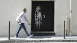 Un homme marche à côté d'une des sorties de secours du Bataclan sur laquelle est apposée l'oeuvre de Banksy, le 25 juin 2018.