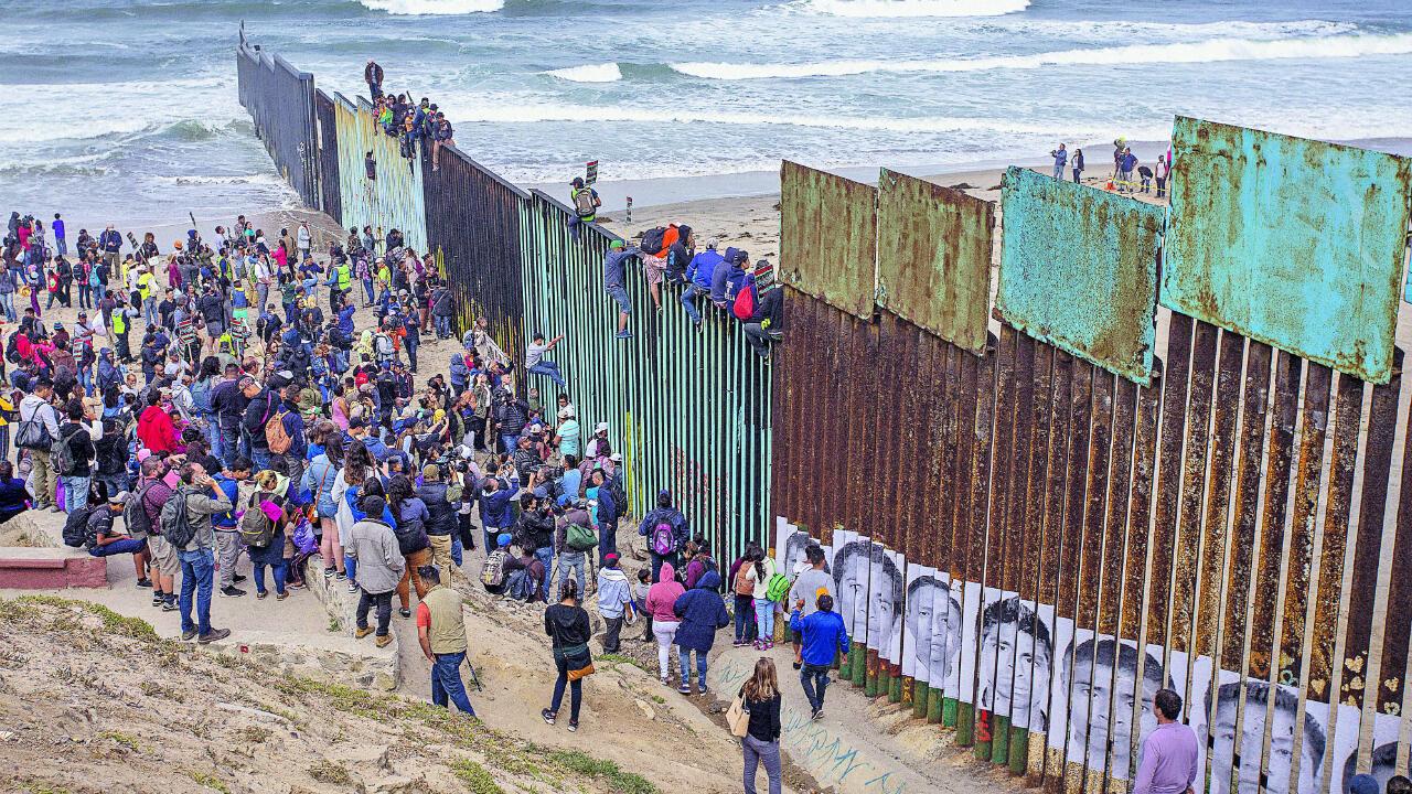 Des gens escaladent une section de la frontière pour se rendre aux États-Unis alors que des membres d'une caravane de demandeurs d'asile d'Amérique centrale se rendent à un rassemblement le 29 avril 2018 à Tijuana, dans la Basse-Californie du Nord.