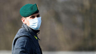 A police officer mans a checkpoint outside the town of Zorlesco in Italy's northern Lombardy region, where residents have been ordered to stay home amid a rapidly worsening coronavirus outbreak.