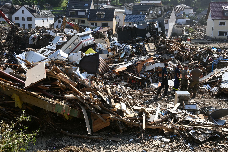 Workers walk amid debris in Kreuzberg, district of Altenahr, Rhineland-Palatinate, western Germany, on July 20, 2021