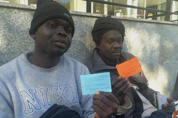 Mohammad et Osmane, deux Soudanais arrivés il y a une semaine à Paris, montrent leur récépissé d'un rendez-vous avec France Terre d'asile.