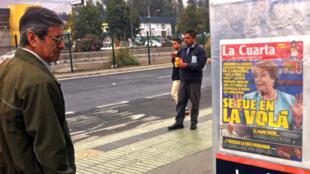 """Un homme regarde la une du quotidien """"La Cuarta"""", jeudi 7 mai à Santiago."""