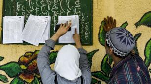 Dos egipcios buscan nombres en un manifiesto de votantes para encontrar los respectivos colegios electorales para votar en un referendo sobre enmiendas constitucionales, en una escuela del barrio de Shubra, en el norte de la capital, El Cairo, Egipto, el 20 de abril de 2019.