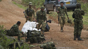 Colombian soldiers stand by equipment, weapons and the corpse of one of ten soldiers killed by the Revolutionary Armed Forces of Colombia (FARC) guerrillas, in a rural area of Buenos Aires, department of Cauca, Colombia, on April 15, 2015