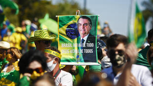 """A supporter brandishes a banner showing Brazilian Jair Bolsonaro, who has repeatedly evoked the threat of a """"coup"""""""