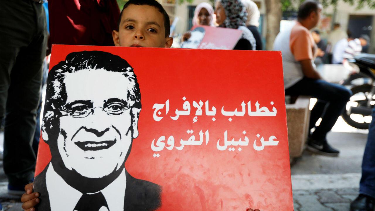 Un garçon tient une pancarte soutenant le candidat à la présidentielle, Nabil Karoui, lors d'un rassemblement demandant sa libération, devant le tribunal de Tunis, le 3 septembre 2019.
