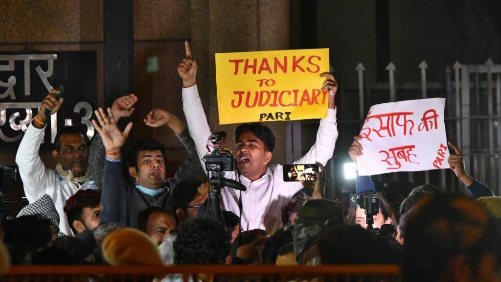 La gente grita consignas mientras sostienen pancartas afuera de la Cárcel de Tihar donde cuatro hombres que fueron condenados por la violación y asesinato de una joven en un autobús en 2012, el 20 de marzo de 2020.