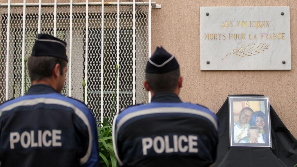 Deux policiers se préparent à observer une minute de silence devant le commissariat d'Ajaccio, en Corse, le 15 juin 2016, en mémoire du couple de policiers tué deux jours plus tôt dans les Yvelines.