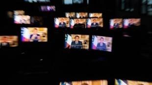 Des écrans de télévision qui retransmettent l'allocution du président Macron, le 13 avril 2020 depuis l'Elysée