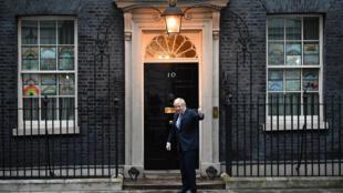 El primer ministro Boris Johnson se despide tras participar en el aplauso a los sanitarios por su labor en la crisis del coronavirus, el 30 de abril de 2020 en Londres, frente al número 10 de Downing Street