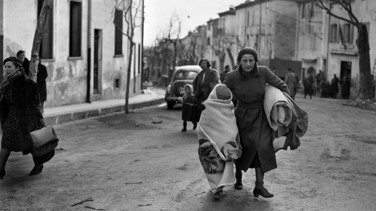 A photo dated February 1939 of a woman and her child arriving on foot in the southeastern French border town of Perthus.