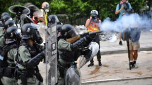 La police antiémeute hongkongaise tire du gaz lacrymogène, le 24 août 2019, pour disperser les manifestants dans le quartier de Kwun Tong.
