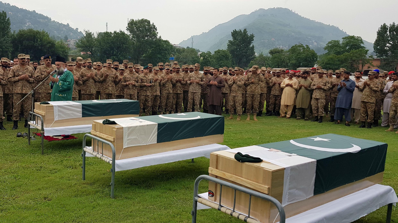 Soldados y civiles del ejército asisten al funeral de tres soldados que, según el Ejército de Pakistán, fueron asesinados en un intercambio de disparos transfronterizo en la Línea de Control (LOC), en el estadio del ejército en Muzaffarabad, Cachemira administrada por P