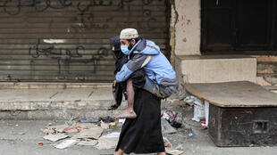A woman carries a disabled man wearing a protective face mask in the Sabra refugee camp in Lebanon where vulnerable Syrian and Palestinian refugees are bracing for the coronavirus