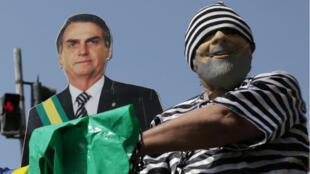 Un manifestante con un disfraz del ex presidente de Brasil, Luiz Inácio Lula da Silva, como prisionero, junto a una imagen de cartón del presidente de Brasil, Jair Bolsonaro, en una manifestación en Rio de Janeiro, Brasil, el 7 de abril de 2019.