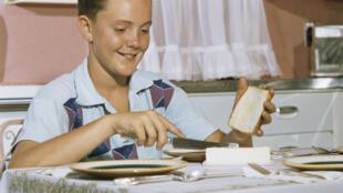 Un jeune garçon en train de tartiner de beurre une tranche de pain.
