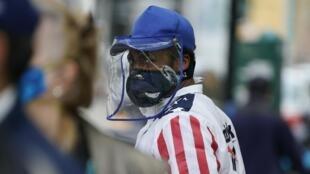 Un hombre con mascarilla y visera protectoras pasa junto a una cola de personas que aguarda la entrega de alimentos por una institución municipal, el 18 de mayo de 2020 en Nueva York