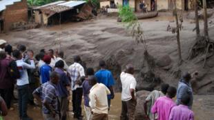 Sobrevivientes observan las consecuencias del deslizamiento a medida que las aguas pasan a través de las casas destruidas, en el distrito de Bududa, Uganda , 12 de octubre de 2018.